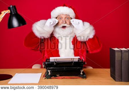 Full Length Photo Of Santa Claus Grey Beard Sit Table Open Mouth Take Off Specs Lamp Book Wear X-mas