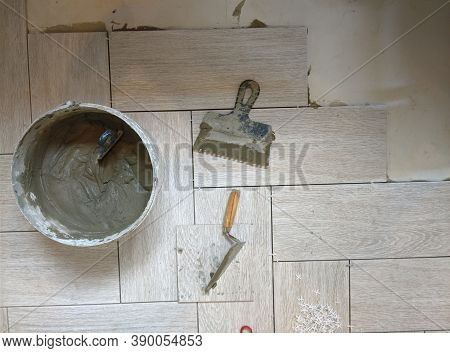 Placing A Porcelain Stoneware Floor With Bricklayer Special Tools, Plastic Tongs And Blue Adjustment