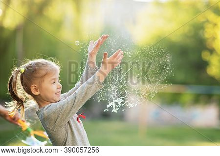 Happy 5 Year Old Child Bursts Soap Bubbles In Garden. Summer Vacation In Nature. Emotional Portrait
