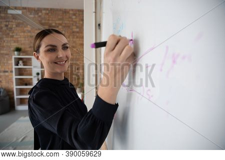 Caucasian professional woman with long dark hair in a bun wearing smart casual blouse in office, writing on a whiteboard, smiling. Hygiene in the workplace during Coronavirus Covid 19 pandemic.