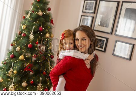 Beautiful Little Girl Having Fun While Playing With Her Mother On Christmas Day, Standing Next To Ni