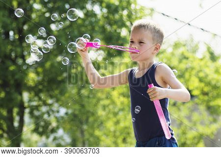 The Cute Blond Hair Boy Is Blowing Soap Bubbles Outdoors On Green Background.