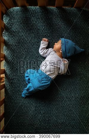 Cute Newborn Baby In Hat In The  Bed. Sleeping Baby On A Dark Background. Closeup Portrait Of Newbor