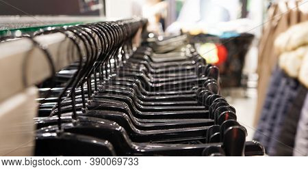 Close-up Modern Fashionable Women's Clothing Hangs On Black Plastic Hangers In A Department Store Of
