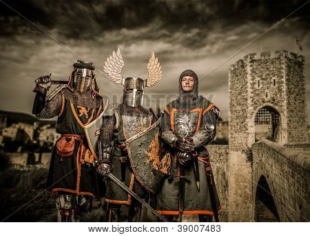 Three knight in armor against Romanesque bridge over river , Besalu