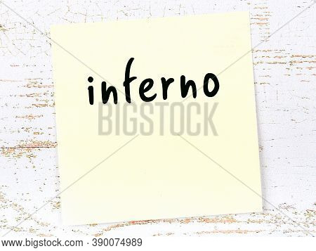 Concept Of Reminder About Inferno. Yellow Sticky Sheet Of Paper On Wooden Wall With Inscription
