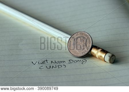 Two Hundred Vietnam Dong Coin On Obverse (vnd) With White Pencil On The Book.