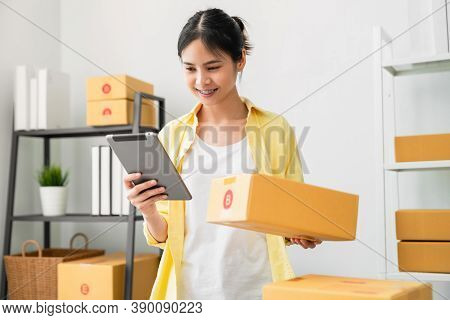 Startup Small Business, A Young Asian Woman Checking Online Order On Digital Tablet And Packing Boxe