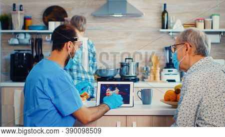 Medical Assistance Pointing At Coronavirus Image On Tablet Pc During Home Visit. Male Nurse Social W