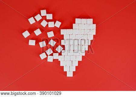 The Broken Heart Made Of Cubes Of Sugar On A Red Background. The Concept Of Problems Associated With