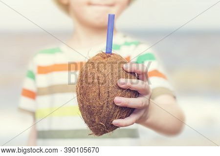 Little Kid Drinking Coconut Water. Little Kid Eating A Coconut. The Child Drinks Coconut Juice From