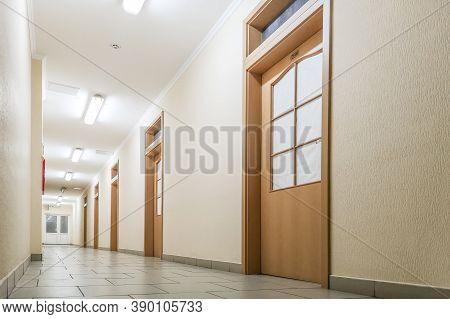 Empty Long Corridor. Empty Office Corridor With Many Doors Of Light Wood
