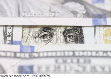 Benjamin Franklin\\\'s Eyes Between Hundred Dollar Banknotes Close-up. Eyes Of Benjamin Franklin Wat