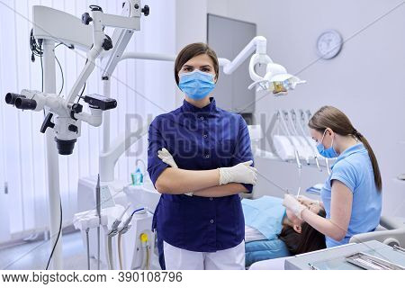Portrait Of Young Female Doctor Dentist In Protective Medical Face Mask With Arms Crossed In Dental