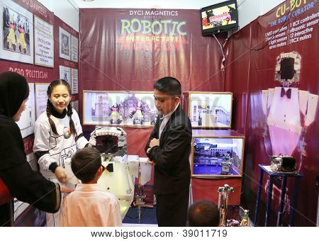 SUBANG JAYA - NOVEMBER 10: Unidentified high students from the Philippines explain their robotic project to visitors at the World Robot Olympaid on November 10, 2012 in Subang Jaya, Malaysia.