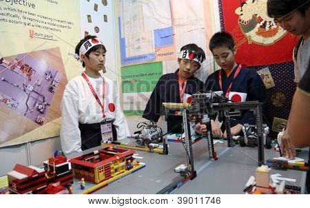 SUBANG JAYA - NOV 10:Unidentified students from Japan show a remote sensing robotic system that control cars to prevent collisions at the World Robot Olympaid on Nov 10, 2012 in Subang Jaya, Malaysia.