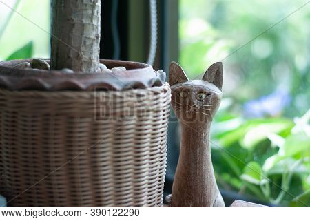 Wooden Craft Long-necked Cat Is Hiding Behide A Plant Basket With Green Background, Cute Crafty
