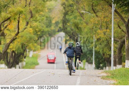 A Teenager, A Boy And His Mom Ride A Bicycle