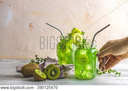 Woman Hand Puts The Glass Jar Of Kiwi Juice Or Smoothie On The Table. Kiwi Mojito Cocktail Or Non-al
