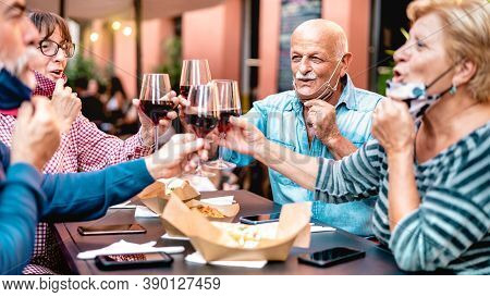 Senior Friends Toasting Wine At Restaurant Bar Wearing Opened Face Mask - New Normal Lifestyle Conce