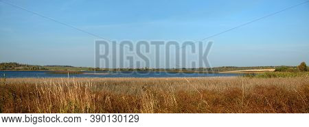 Quiet Backwater On A Rural Lake With Panoramic View Of The Village And Forest Far Away On The Horizo