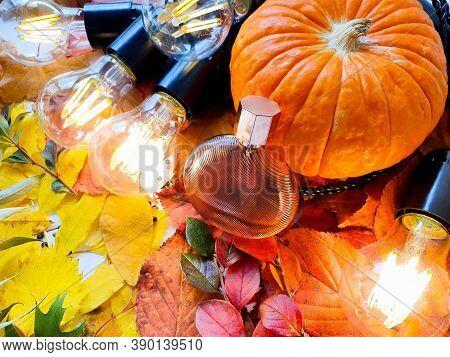 Perfume Bottle, Pumpkin And Magic Lights On Bright Autumn Leaves. Eau De Toilette. Fall Flatlay, Moc