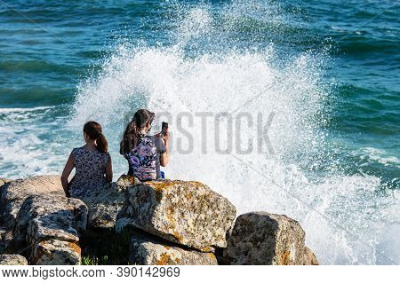 Portonovo, Spain - August 21, 2020: A Young Woman Takes A Picture With Her Smartphone While Enjoying