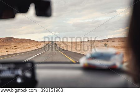 Car Driving Through Desert Landscape On Overcast Day, View From Passenger Seat, Blurred Dashboard Fo