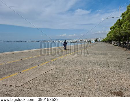 An Orthodox Priest Walking Fast At The Waterfront In Thessaloniki, Greece. Day View Of A Greek Clerg