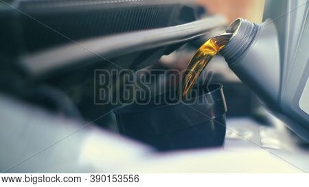 Pouring fresh new clean synthetic oil into car's engine, closeup. Shallow DOF.
