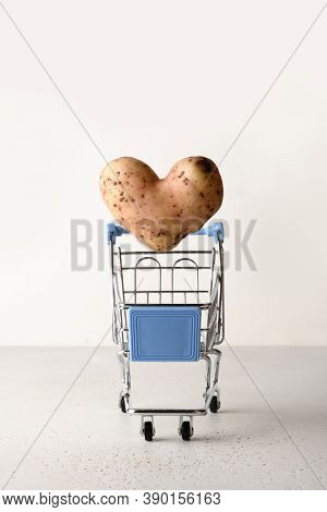 Organic Potato In Shape Of Heart Flying Into Grocery Cart On White Background. Homegrown Ugly Vegeta