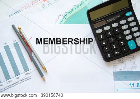 The Word Membership Is Written In A Notebook With Graphs Next To A Calculator And A Financial Graph.