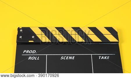 Clapperboard Or Movie Slate With Black&yellow Color And Film Roll On Yellow Background. It Is Used I