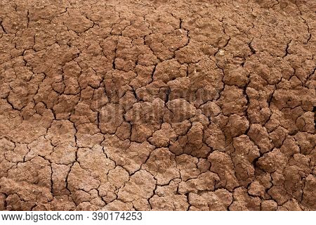 The Natural Backdrop Of Red, Cracked, Dry Earth. Clay Barren Dry Land Close-up. A Lifeless Desert On