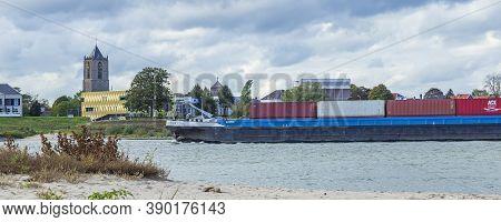Tiel, Netherlands - October 4, 2020: Skyline Of City Tiel With Cargo Ships Crossing The Waal In Betu