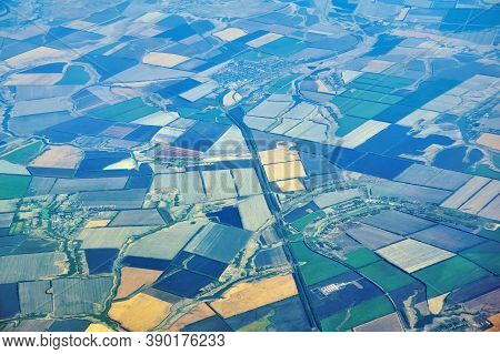Aerial View Of A Densely Populated Region With Multi-colored Fields And Settlements