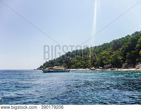 A Pleasure Boat Unloads Tourists On The Shores Of The Andaman Sea In A Hot, Sunny Day.