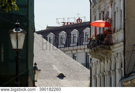 Bucharest, Romania - July 23, 2020 A Red Umbrella On A Sunny Day On The Balcony Of An Old House In T