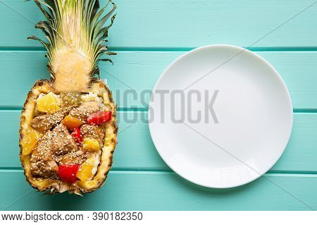 Pineapple Rice With Chicken And Vegetables, Top View. Tasty Exotic Meal And White Empty Plate. Creat