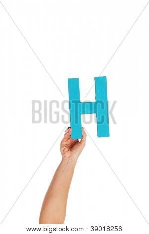 Female hand holding up the uppercase capital letter H isolated against a white background conceptual of the alphabet, writing, literature and typeface