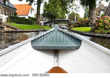 Photo Taken From A Boat, The Prow Of The Boat Visible, Blurred Background Of The Water Channel And T