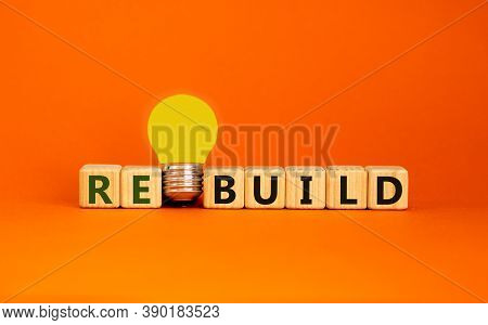 Wooden Cubes With Word 'rebuild'. Yellow Light Bulb. Beautiful Orange Background. Business Concept.