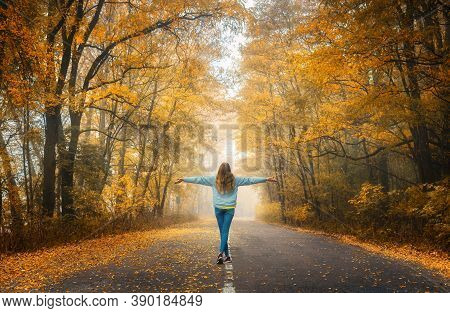 Happy Young Woman On The Road In Beautiful Autumn Forest In Fog At Sunset. Landscape With Alone Girl
