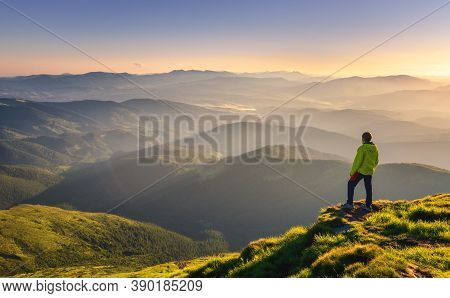 Sporty Man On The Mountain Peak Looking On Mountain Valley With Sunbeams At Colorful Sunset In Autum