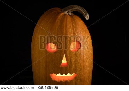 Halloween Pumpkin With Luminous Glowing Eyes  Isolated On A Black Background. Jack-o'-lantern.
