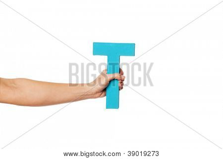 Female hand holding up the uppercase capital letter T isolated against a white background conceptual of the alphabet, writing, literature and typeface