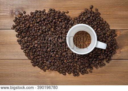 Cup With A Portion  Of Instant Or Granulated Coffee And Scattered Coffee Beans On Wooden Table. Conc