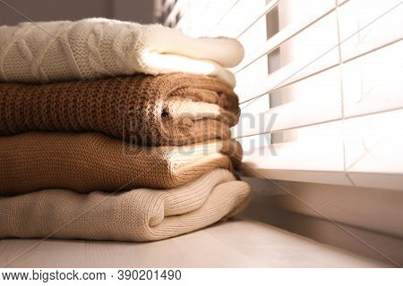 Stack Of Folded Warm Sweaters On Window Sill Indoors, Closeup. Space For Text