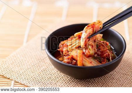 Korean Food, Kimchi Cabbage In A Bowl Eating With Chopsticks