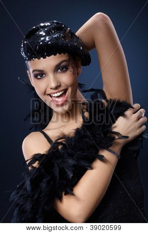 Attractive woman enjoying posing and smiling in extravagant party outfit, fancy makeup, black sequin hat and feather boa. poster